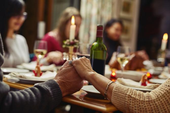 group holding hands around Shabbat table with candles and wine visible