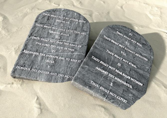 tablets of ten commandments in English on sandy ground