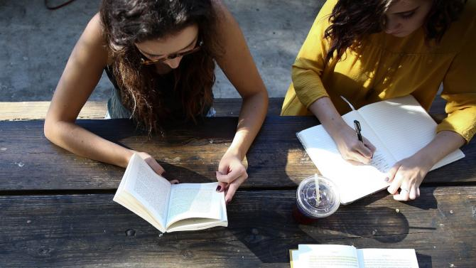 two people studying together at a wooden table, reading a book and taking notes