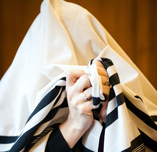 Person covering their head with a white tallit with black stripes