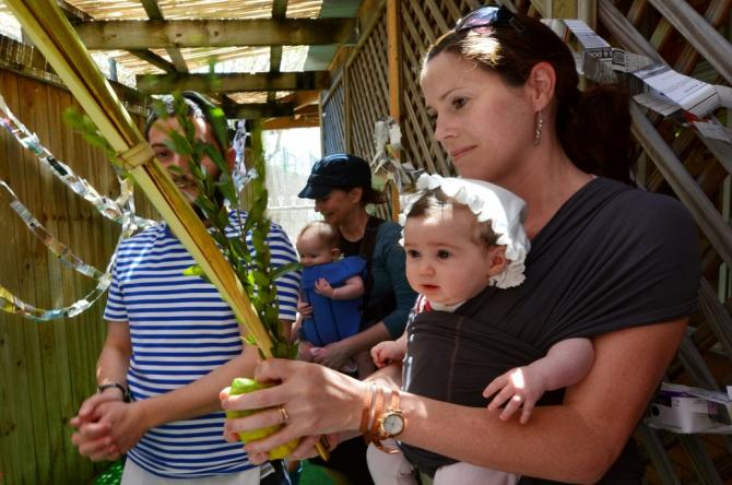 woman with baby in front carrier holding lulav and etrog in sukkah