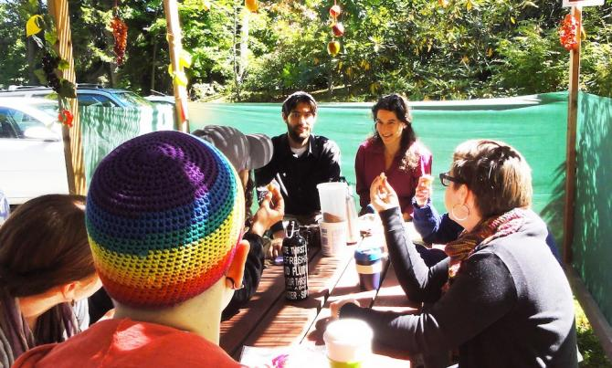 Group of people seated around a table inside a sukkah