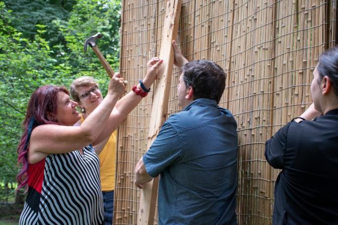 Woman nailing board onto a sukkah frame