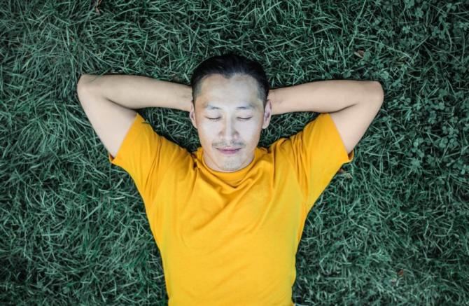 man in yellow shirt sleeping on grass with hands behind his head
