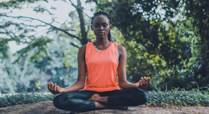 woman of color meditating seated in lotus position in forest