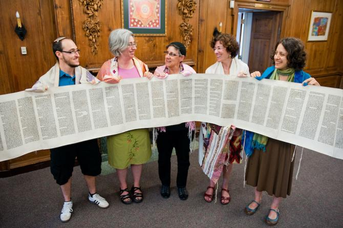 five people in tallitot holding a Torah scroll rolled open to display its text