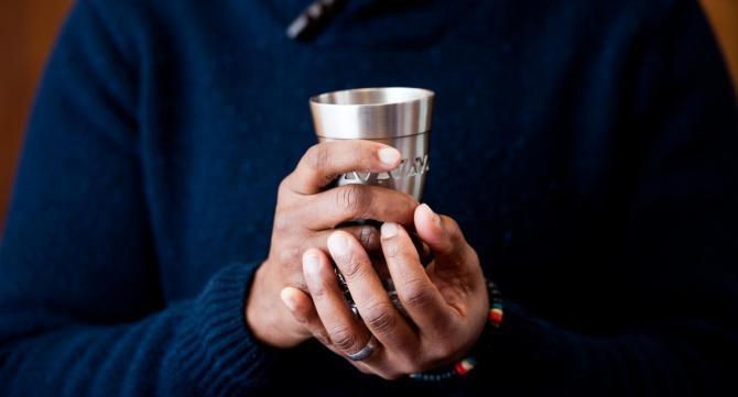 Hands holding kiddush cup