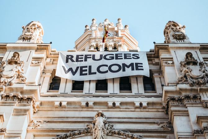"""marble building hung with """"refugees welcome"""" banner"""