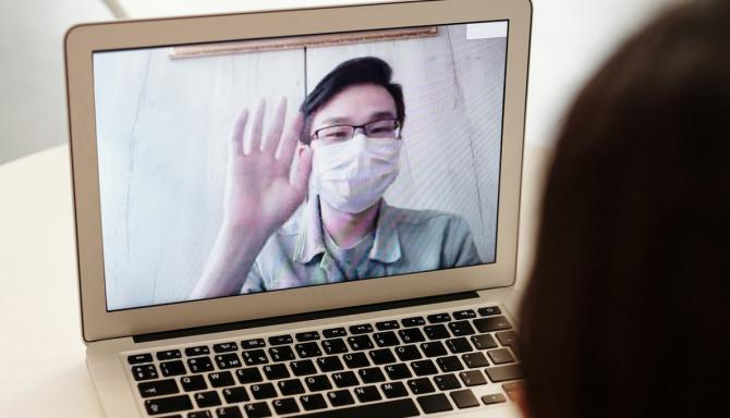 laptop screen showing masked person raising hand in greeting