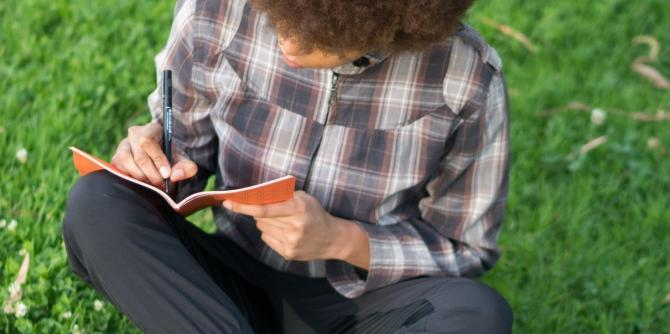 person seated in grass writing in journal