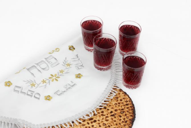 Four cups of wine next to matzah