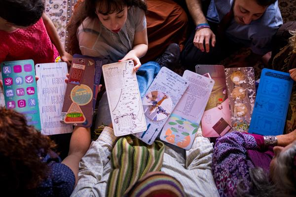 Overhead view of children with hand-drawn Passover haggadahs