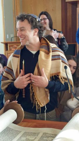 Rabbi Joshua Boettiger in tallit in front of Torah scroll